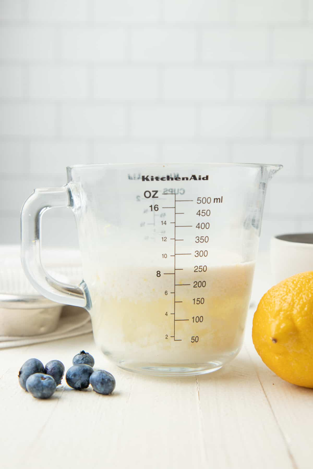 Curdled plant-based milk sits in a glass measuring cup.