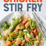 "Stir fry sits in a bowl with chopsticks. A text overlay reads, ""Healthy Chicken Stir Fry""."