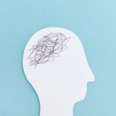 A white paper cut out of a head with scribbles where the brain would be