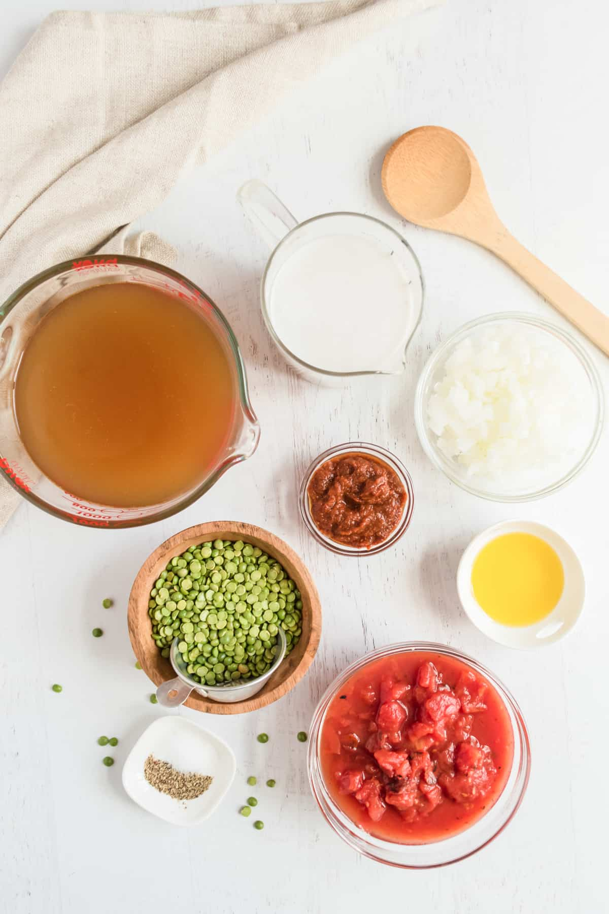 Ingredients to make curry sit together - vegetable broth, coconut milk, tomatoes, red curry paste, split peas, butter, and onion.
