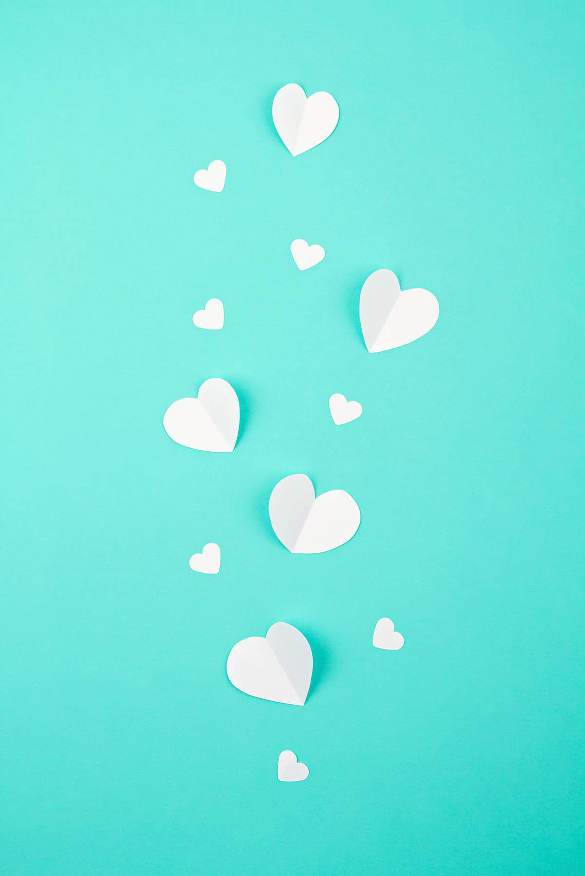 Paper hearts on a teal background