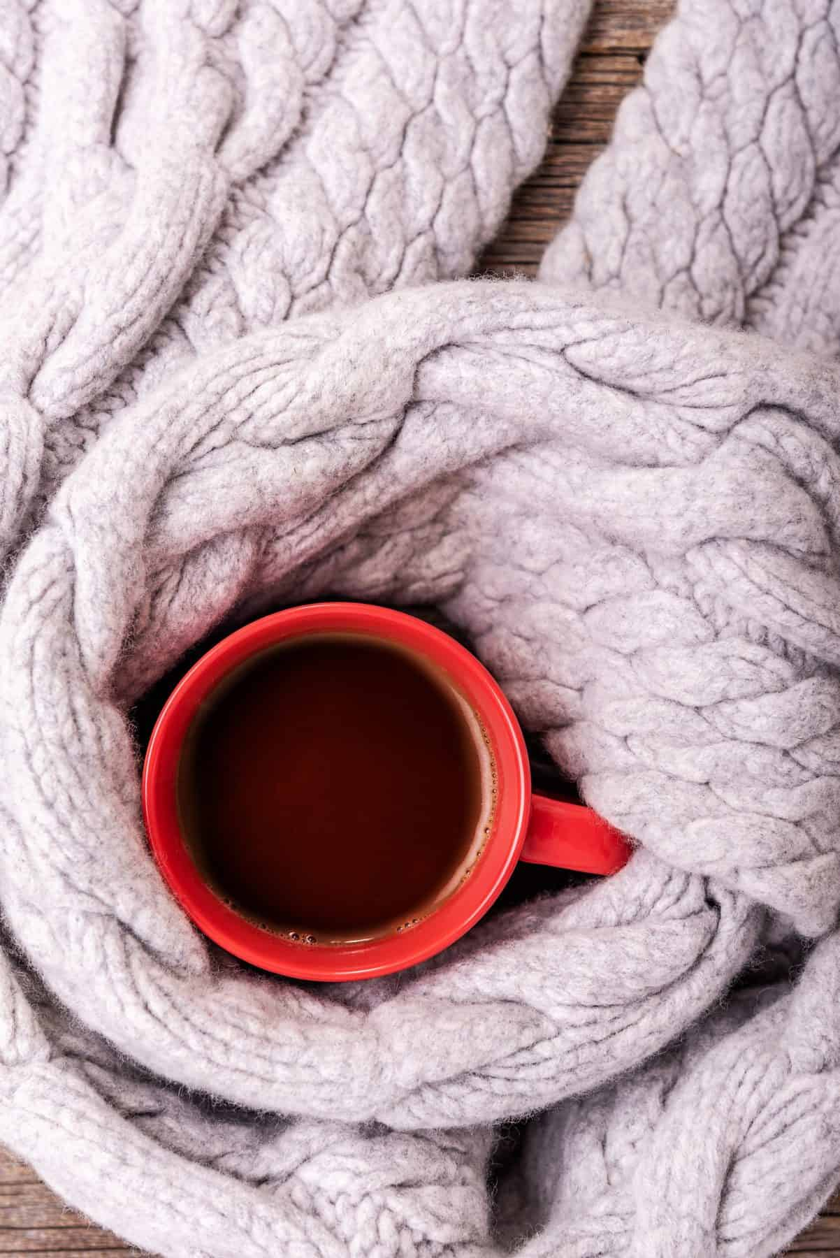 A scarf is wrapped around a red cup full of tea.