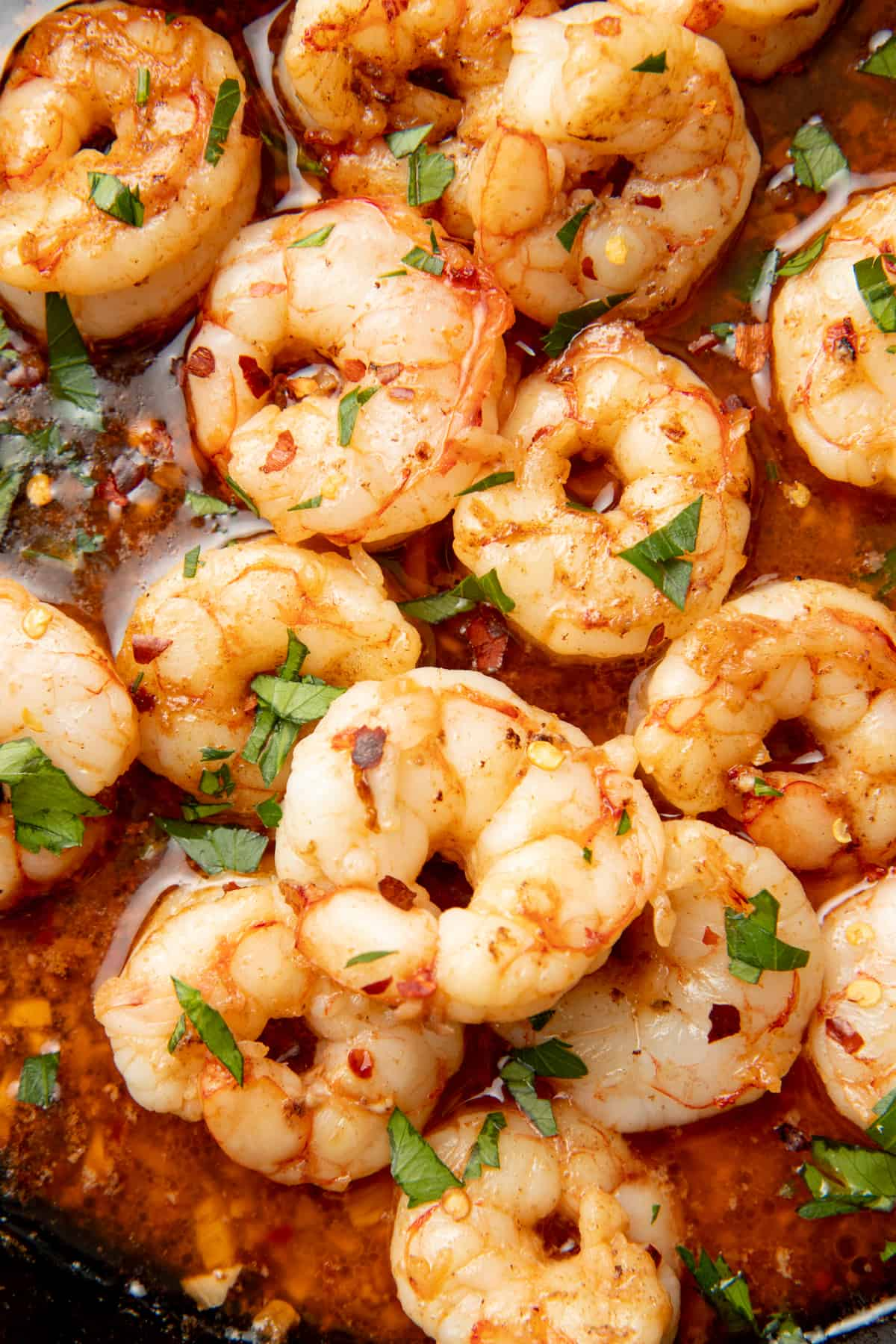 Cooked shrimp sit in sauce.