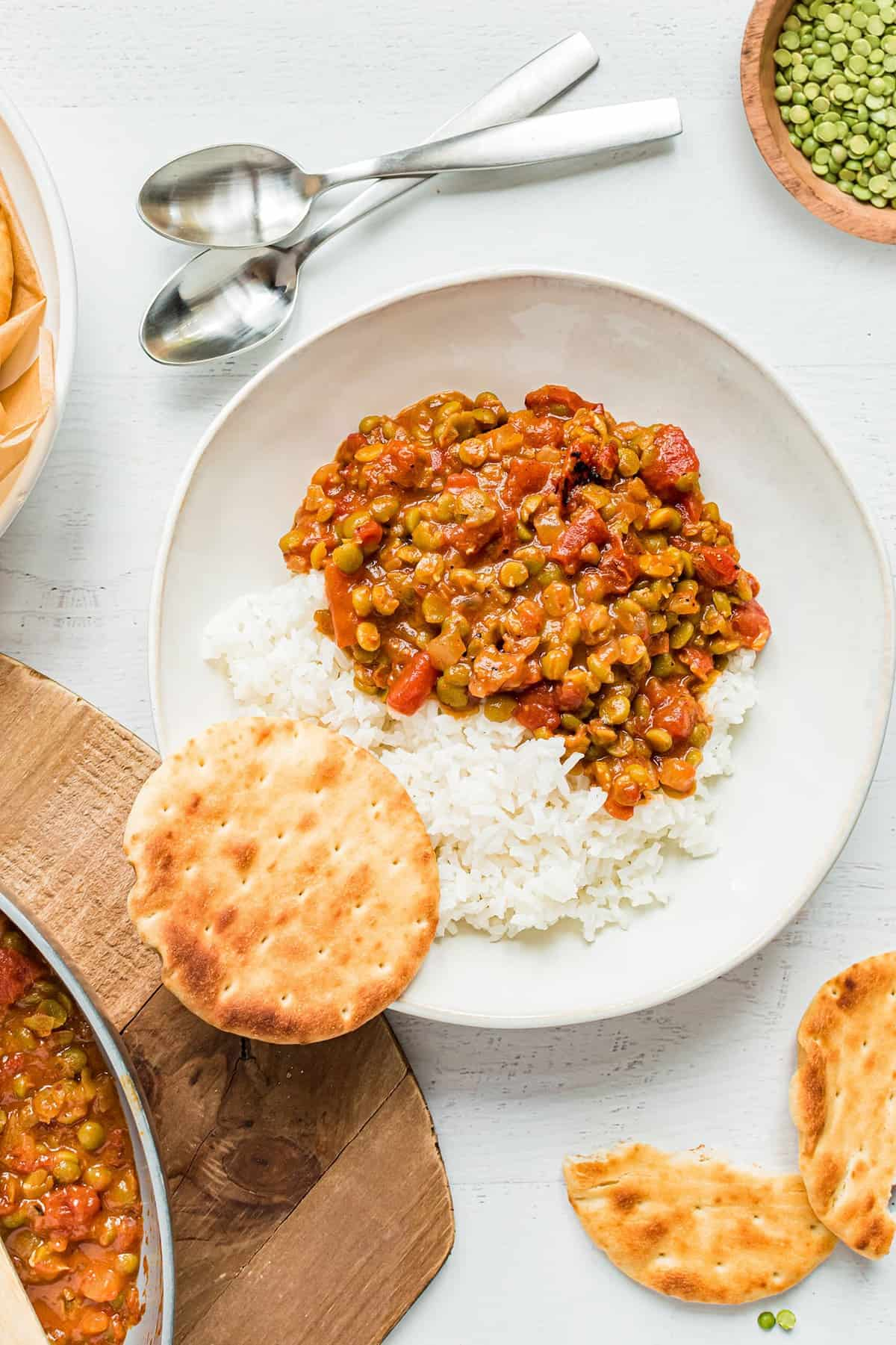 Split Pea Curry sits in a bowl over rice. Naan bread sits nearby.