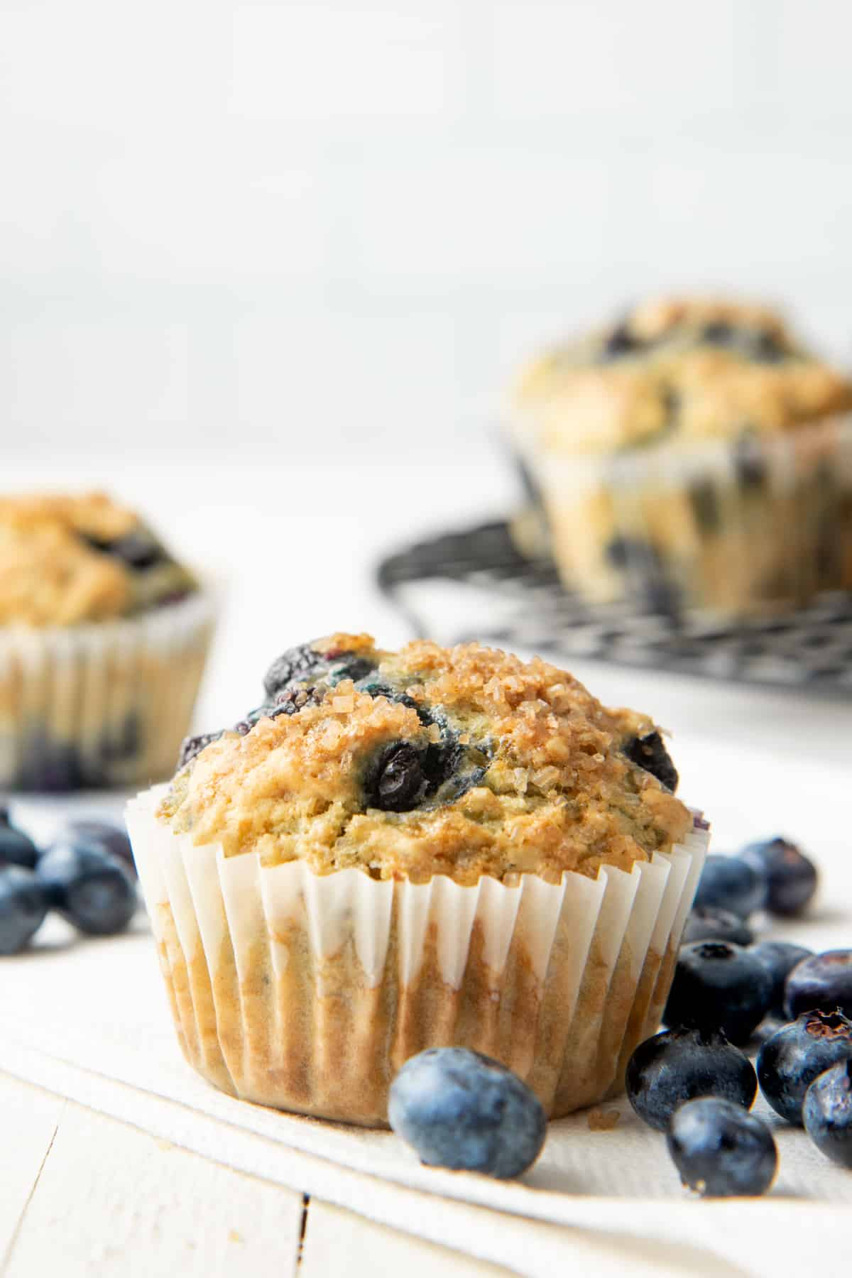 A baked Vegan Blueberry Muffin sits surrounded by fresh blueberries.