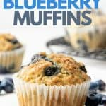 "A freshly baked Vegan Blueberry Muffin sits surrounded by fresh blueberries. A text overlay reads, ""Vegan Blueberry Muffins""."