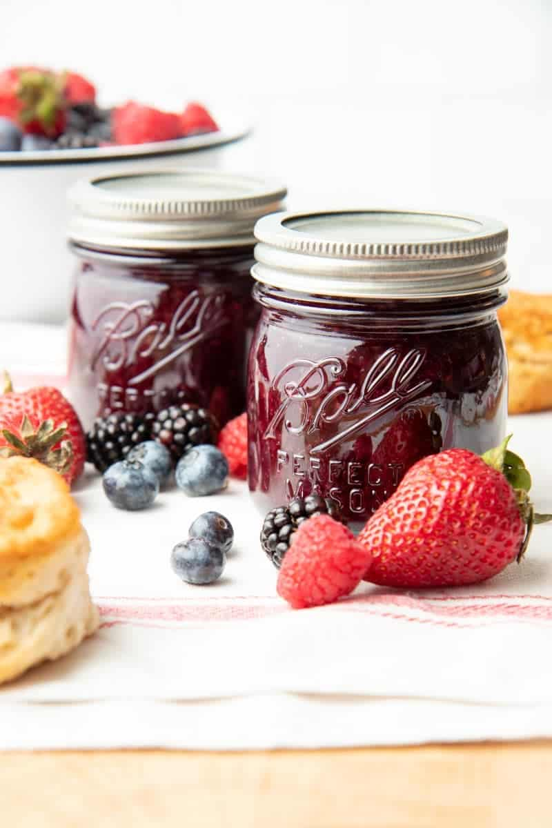 Close-up of two Ball Perfect Mason jars filled with finished mixed berry jam surrounded by fresh berries and biscuits.