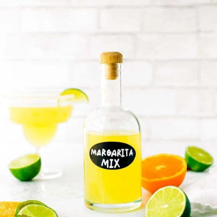 Homemade margarita mix in a glass bottle surrounded by fresh cut limes and oranges.