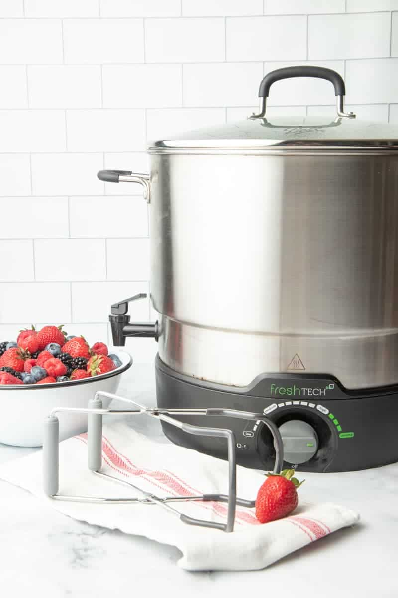 FreshTech water canner sitting on a kitchen counter with jar lifters and fresh berries beside it.