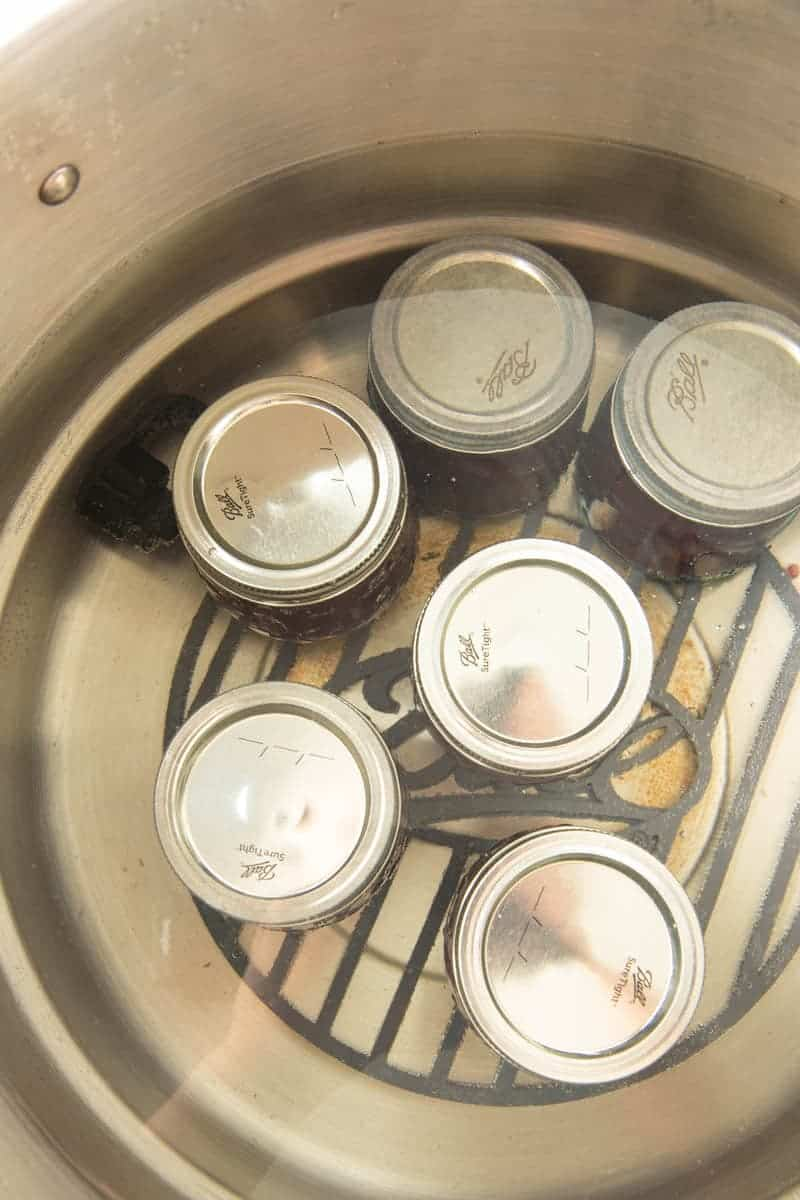 Overhead of six full ball jars of mixed berry agave jam in water canner.