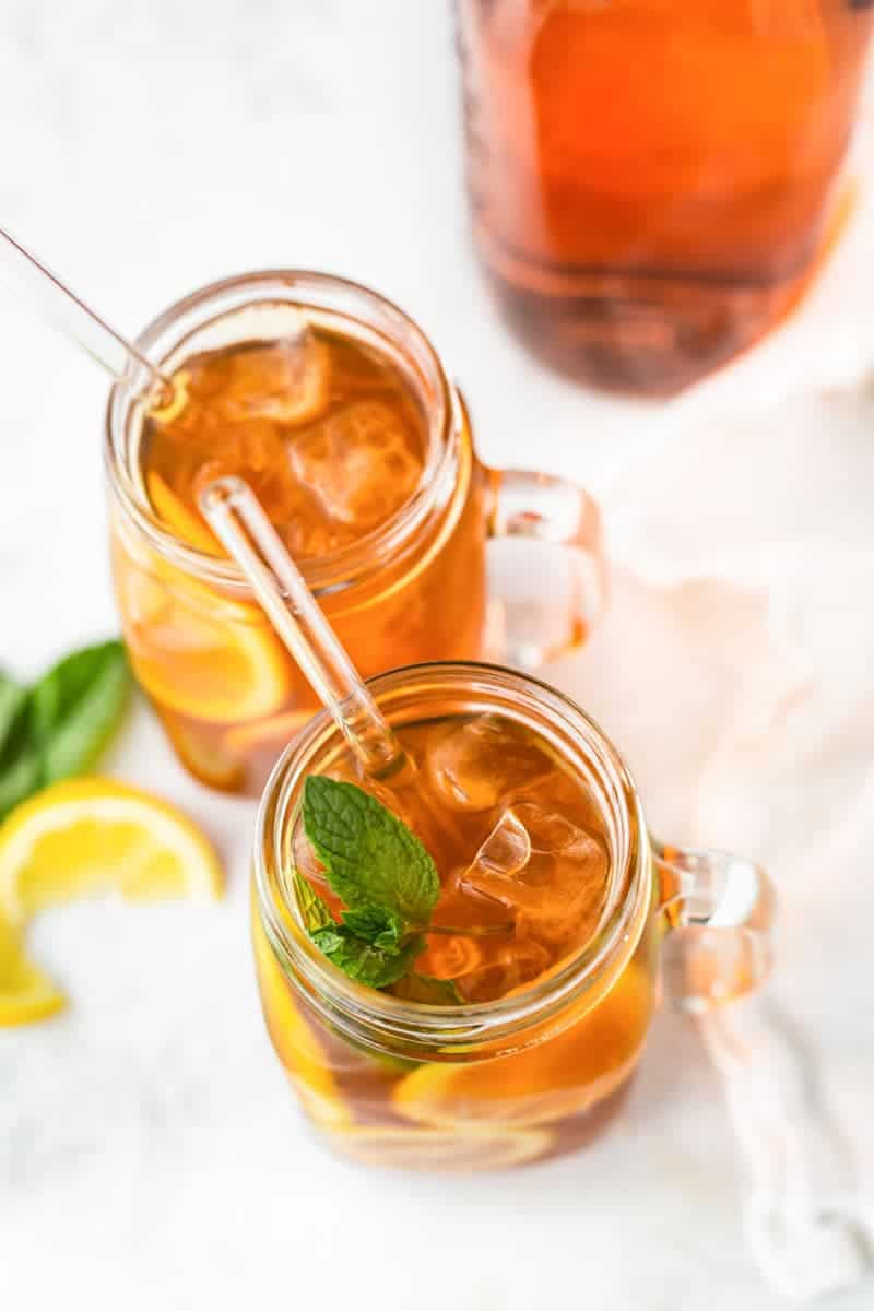 Close view of brewed sun tea over ice with mint garnish and glass straw.