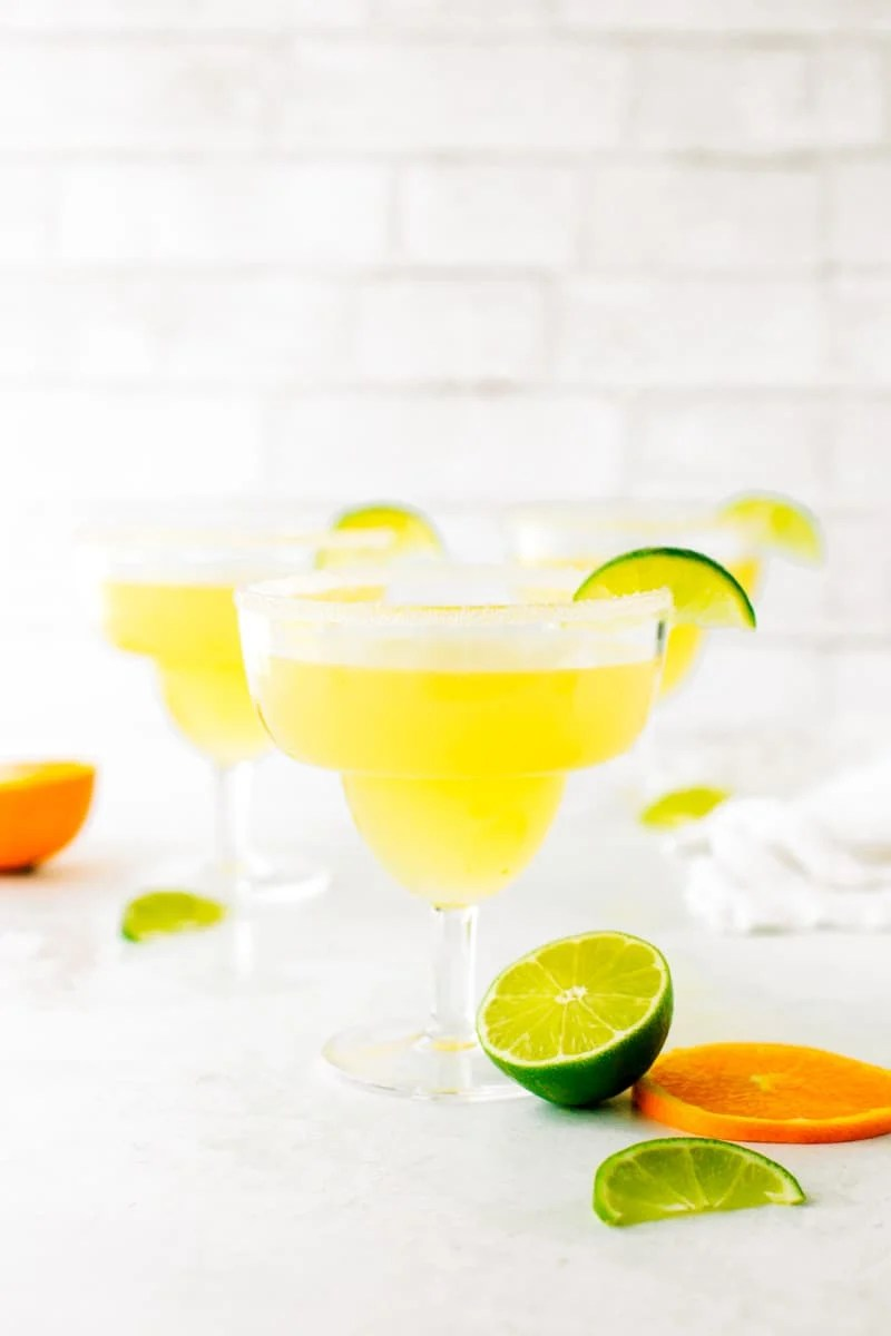 Homemade margarita in a margarita glass with a wedge of lime and a salt rim.