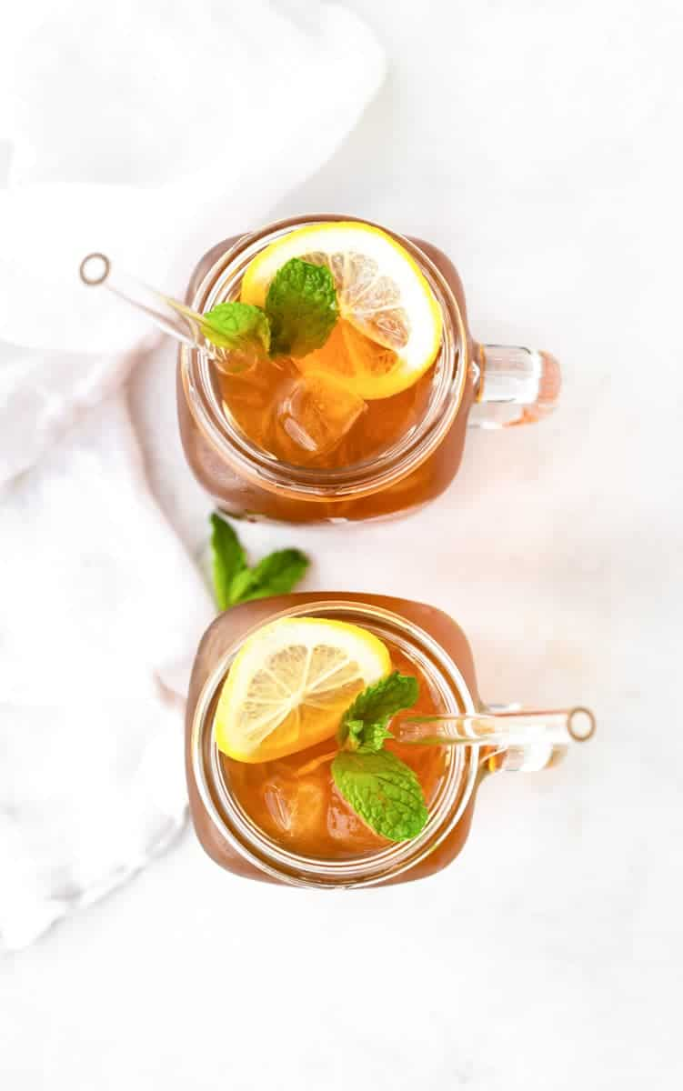 Overhead of two glasses of sun tea garnished with lemons and mint.