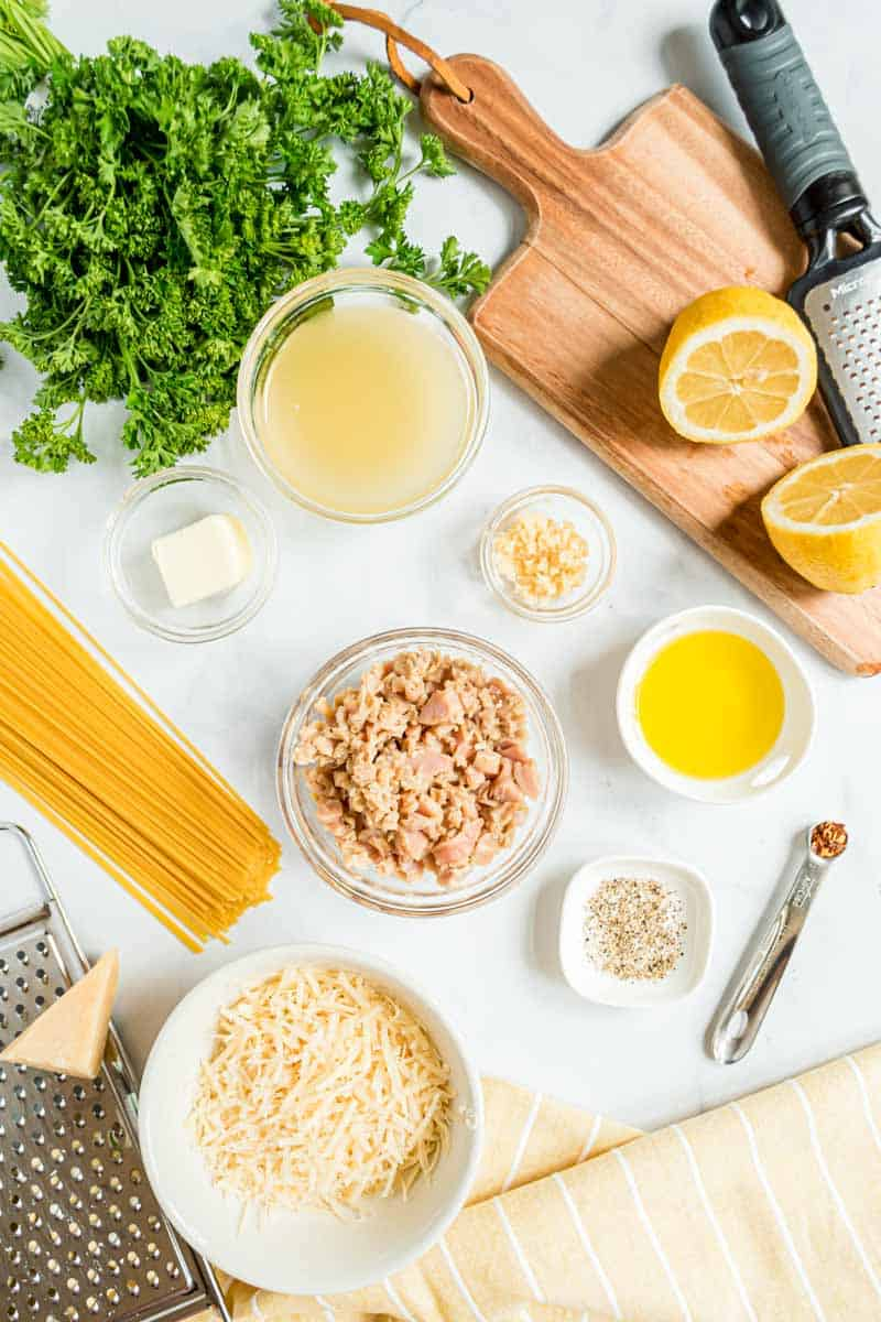 All ingredients needed to make spaghetti with canned clams sit in individual bowls, alongside tools such as a wooden cutting board and microplane.