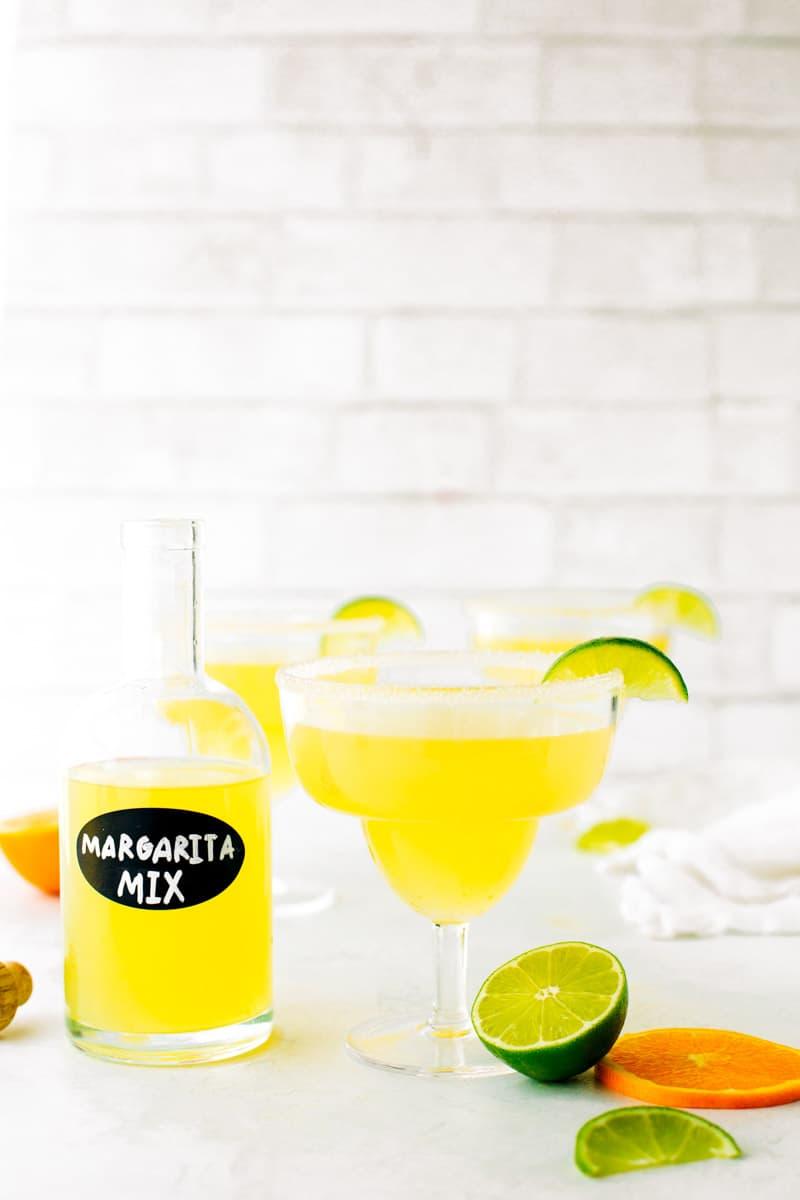 Bottle of homemade margarita mix next to margarita with a salt rim and fresh citrus.