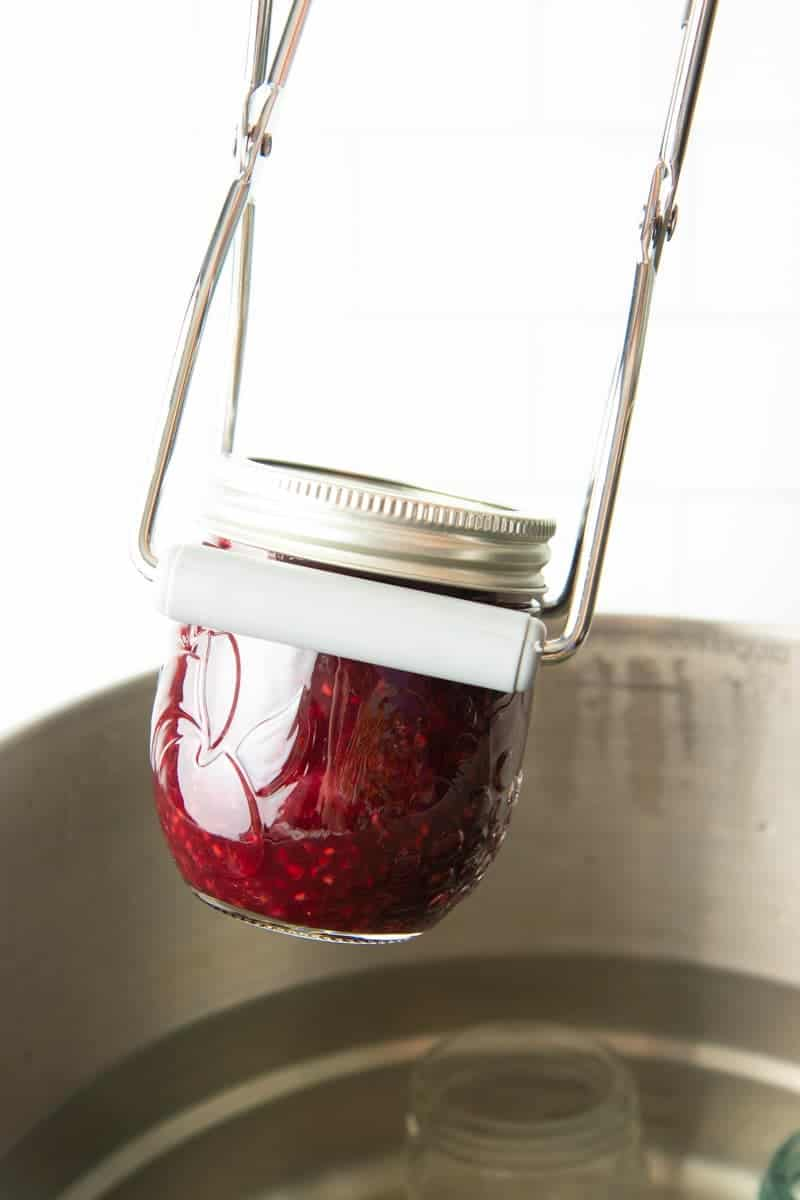 Lifting jar of jam out of waterbath canner.