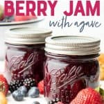"Close-up of two Ball Perfect Mason jars filled with finished mixed berry jam surrounded by fresh berries and biscuits. A text overlay reads ""how to Can Naturally Sweetened Berry Jam with Agave."""