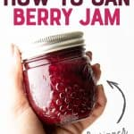 "Close-up of a hand holding a full jar of mixed berry agave jam. A text overlay reads ""Step-by-Step How to Can Berry Jam."""
