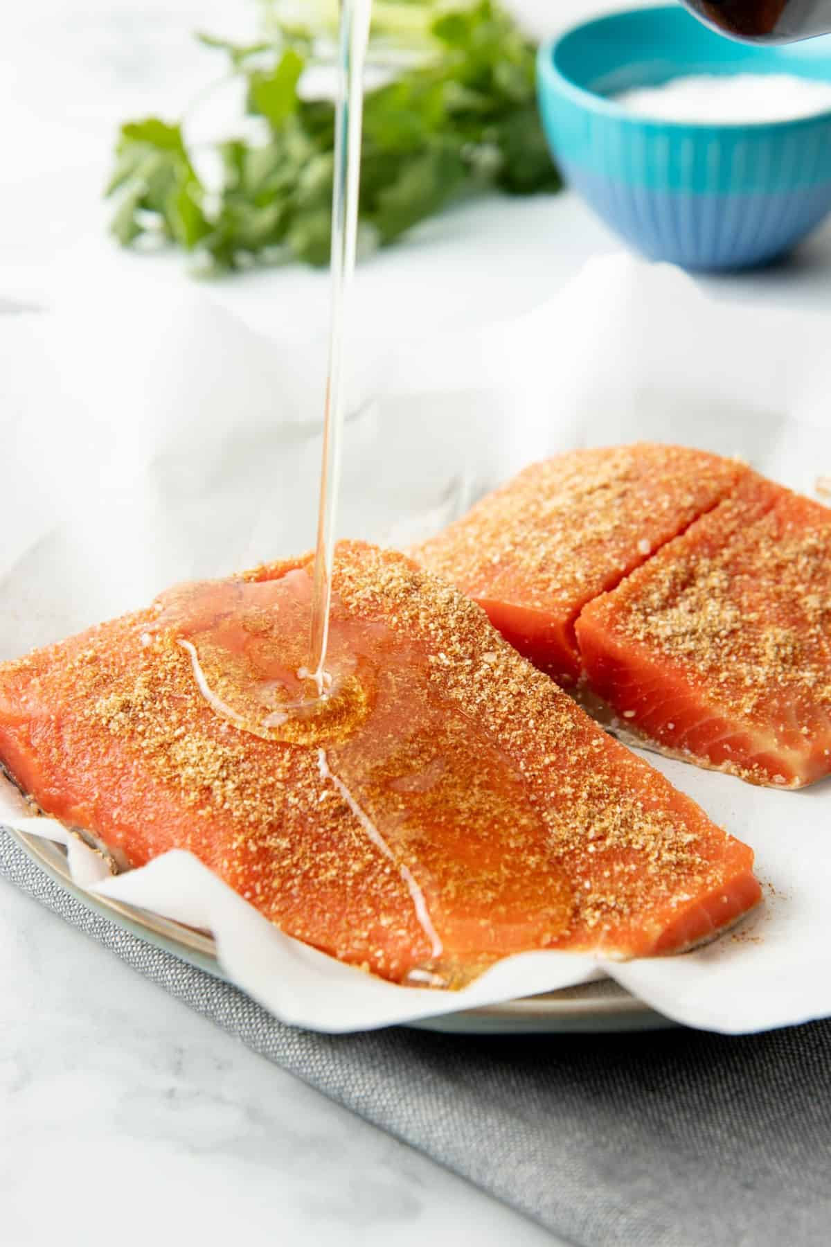 Close-up of oil pouring onto two seasoned salmon fillets.