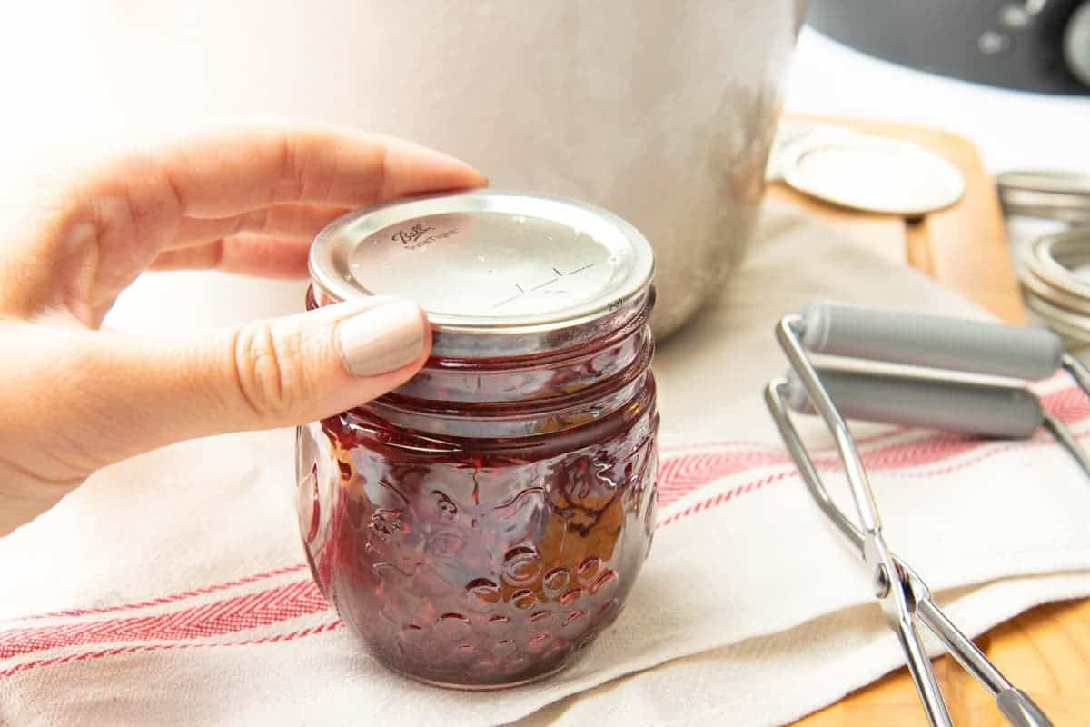 Hand putting lid on full jar of mixed berry jam with jar lifters alongside.