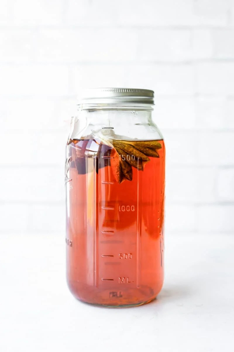 Iced tea in a tall Ball jar with tea bags floating on top.