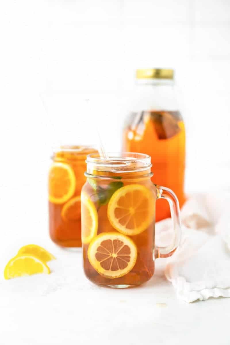 Finished sun tea in mason jar glasses with lemon wheels.