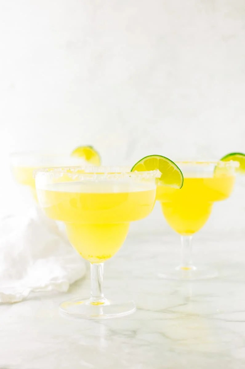 Three homemade margaritas in margarita glasses garnished with a wedge of lime and a salt rim.
