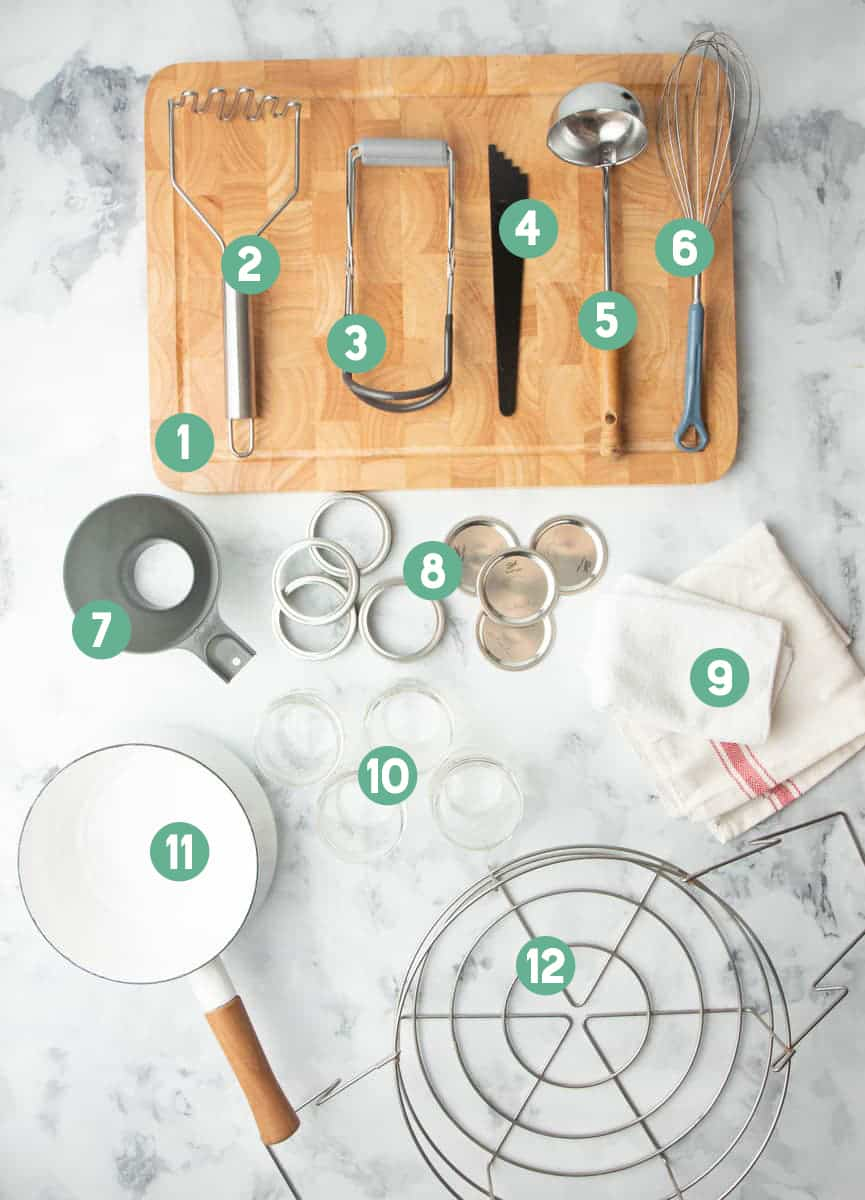 Tools for canning such as canning lids, ball jars, jar lifters, wide mouth funnel, laid out and numbered 1 through 12.
