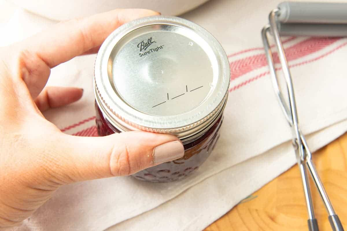Close-up of hand tightening ring on full Ball jar of mixed berry agave jam.