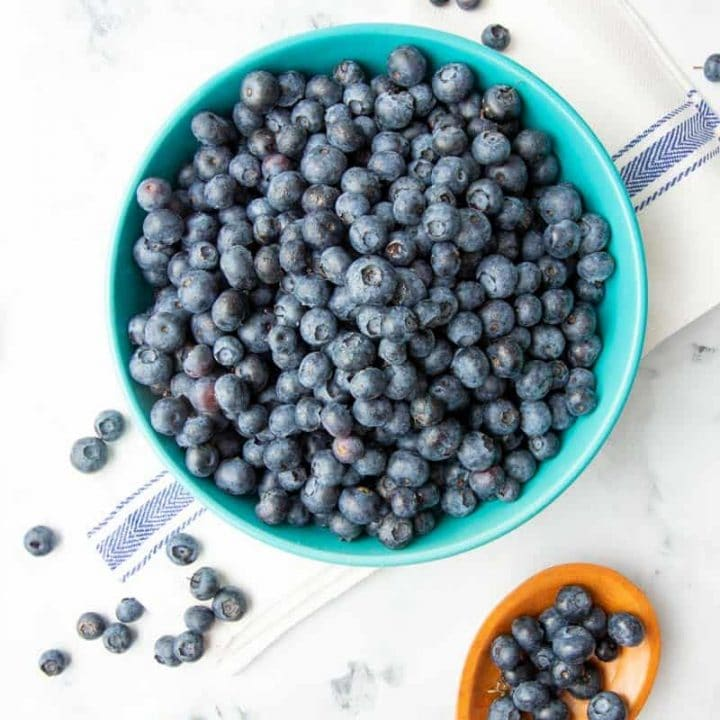 Overhead of fresh blueberries in a large bowl with a wooden spoon filled with blueberries alongside.