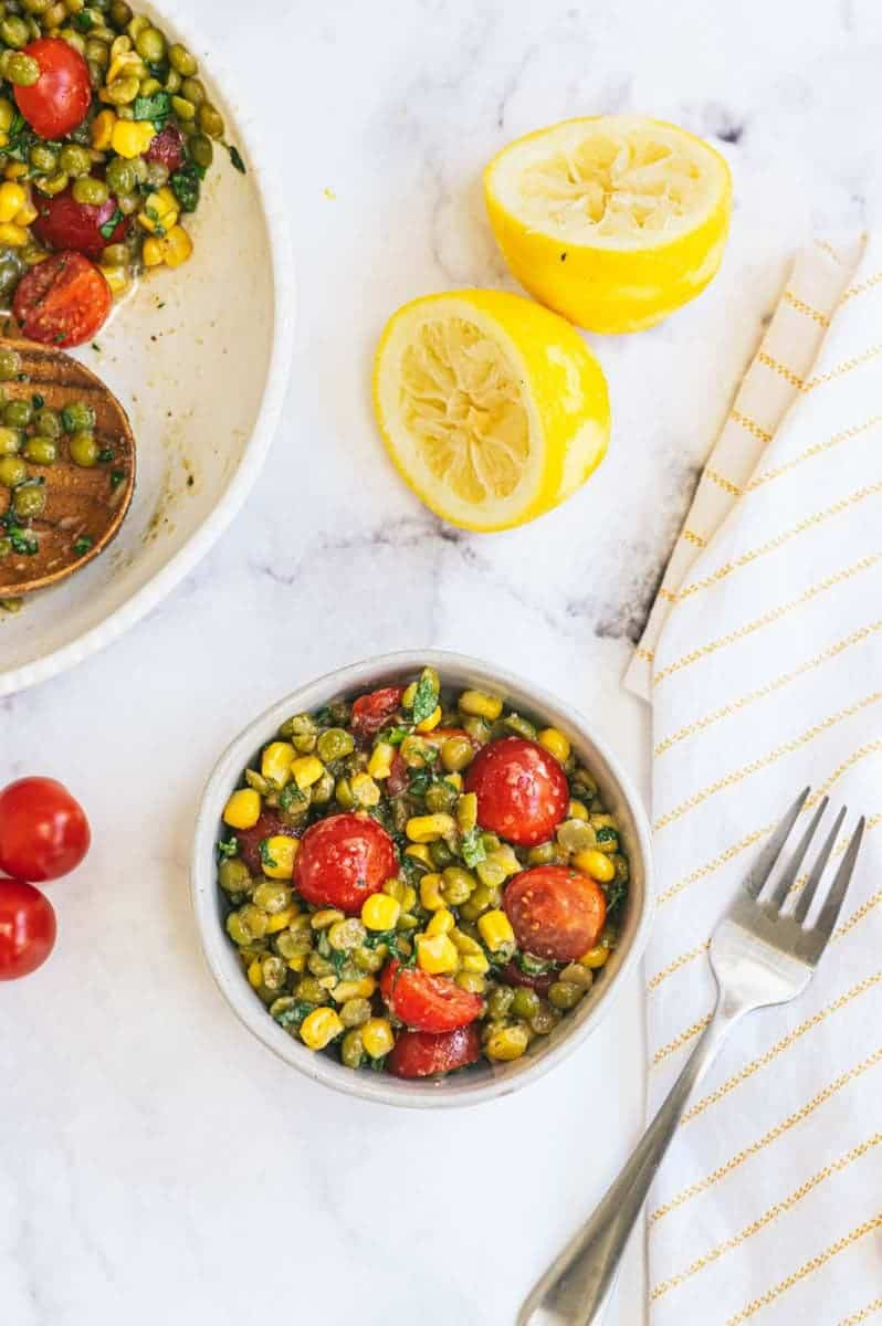 A single serving of summer split pea salad in a bowl with a fork alongside the larger serving bowl, fresh tomatoes, and zested and juiced lemon halves.