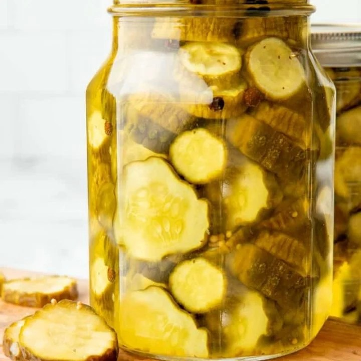 Close-up of full quart jar of canned bread and butter pickles on a wooden cutting board with fresh pickles beside it.