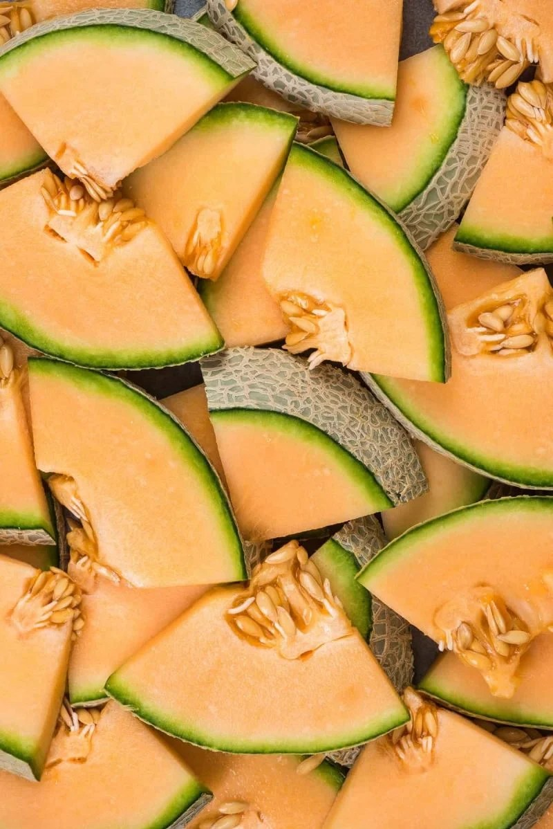 Overhead of cantaloupe circles sliced into quarters and lying flat in a colorful jumble.