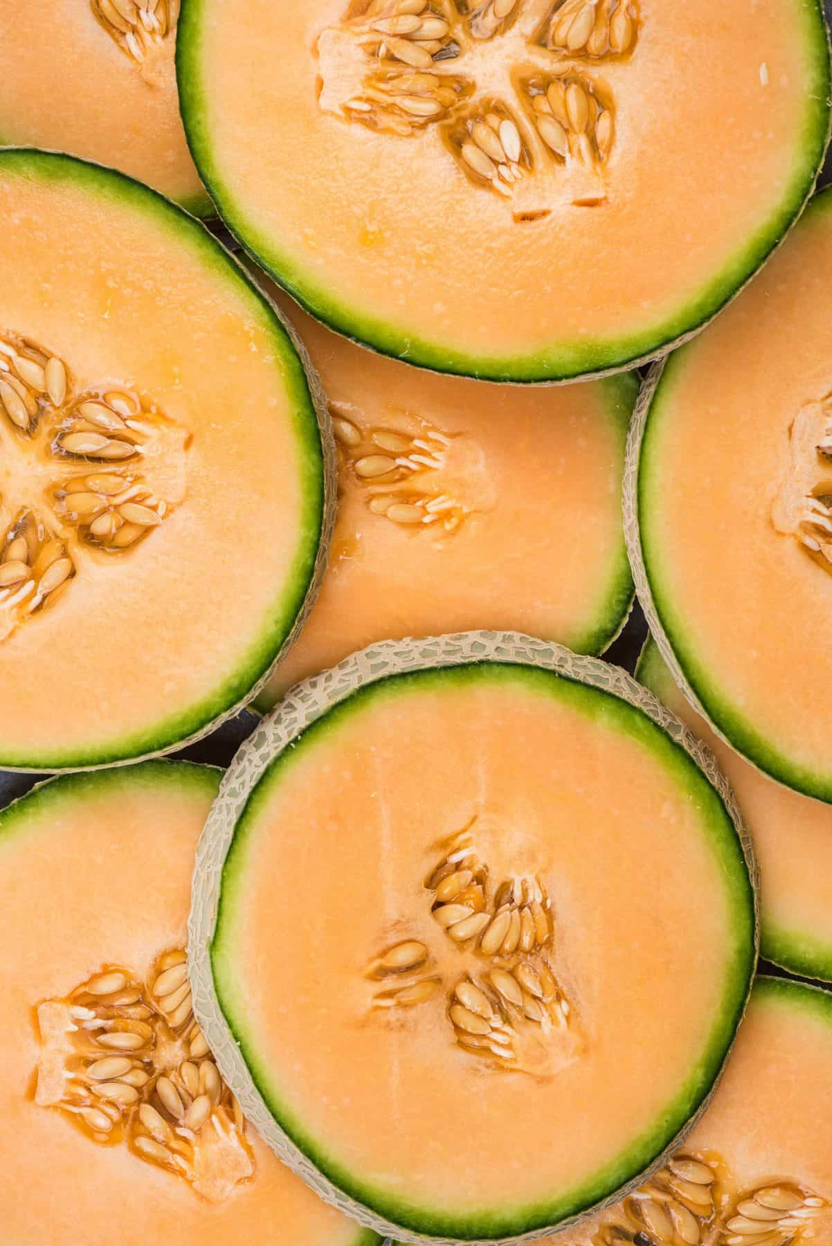 Overhead of full circle cantaloupe slices with their seeds stacked in two layers.