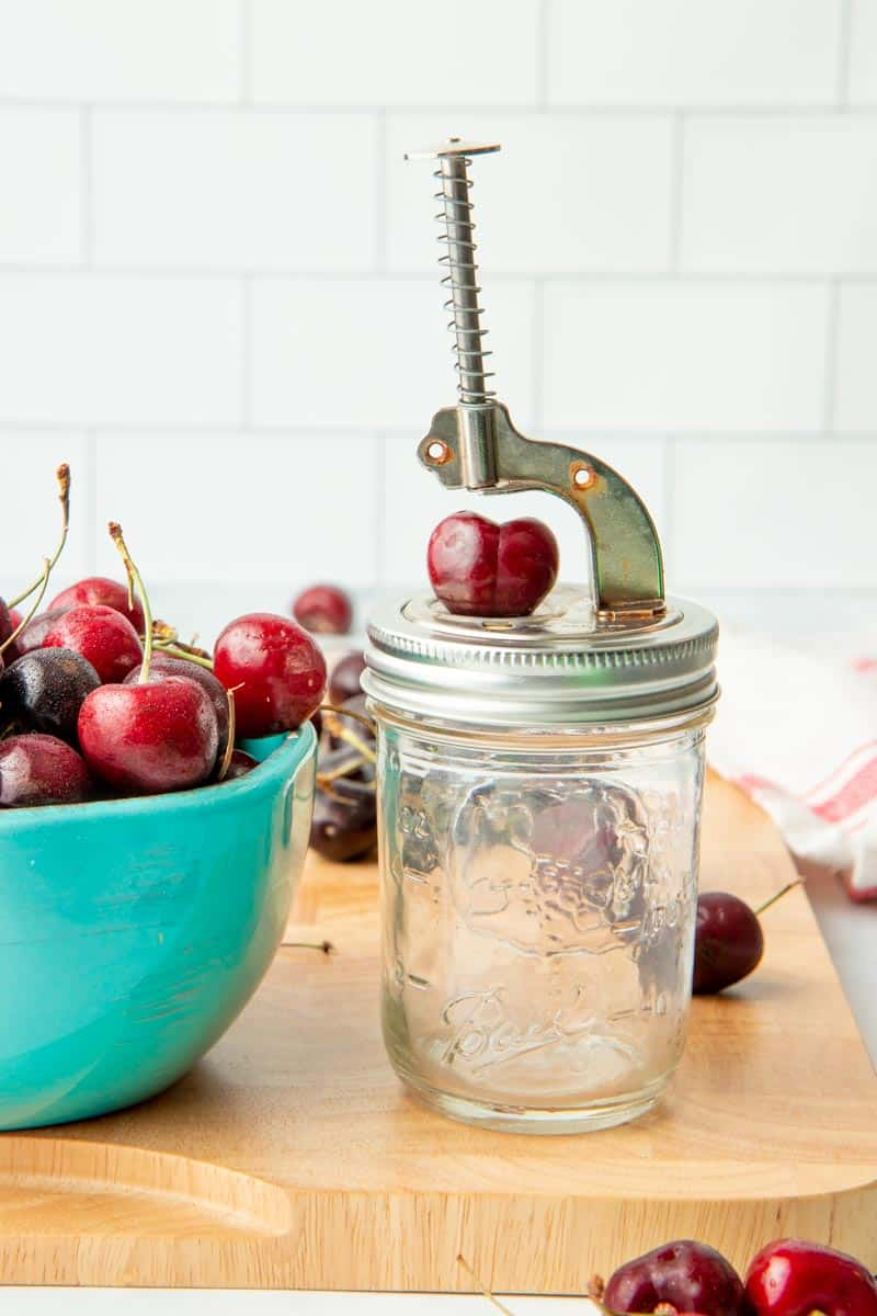 Mason jar push button cherry pitter with a cherry on it ready to be pitted, next to a bowl of fresh fruit.
