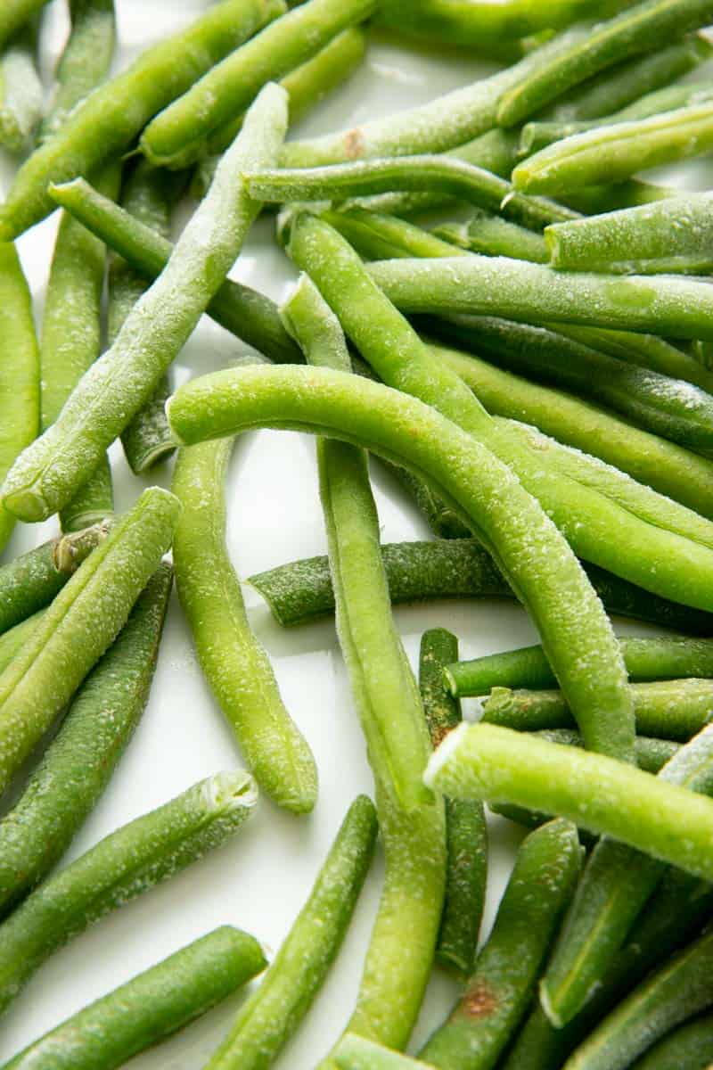 Close-up of individually frozen string beans on a baking sheet.