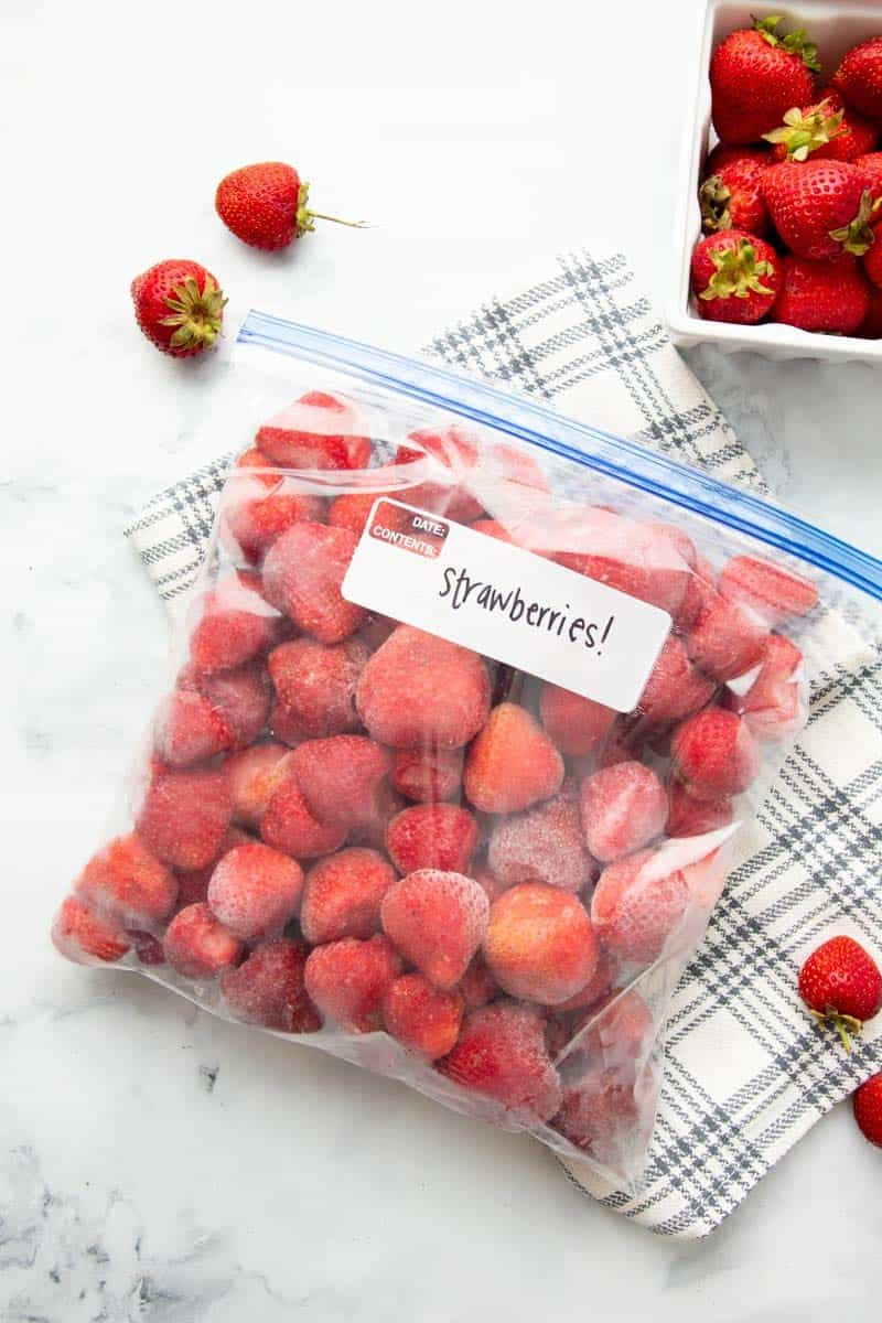 Freezer bag labeled strawberries lying on it's side, closed, and full of whole, hulled, individually frozen strawberries.