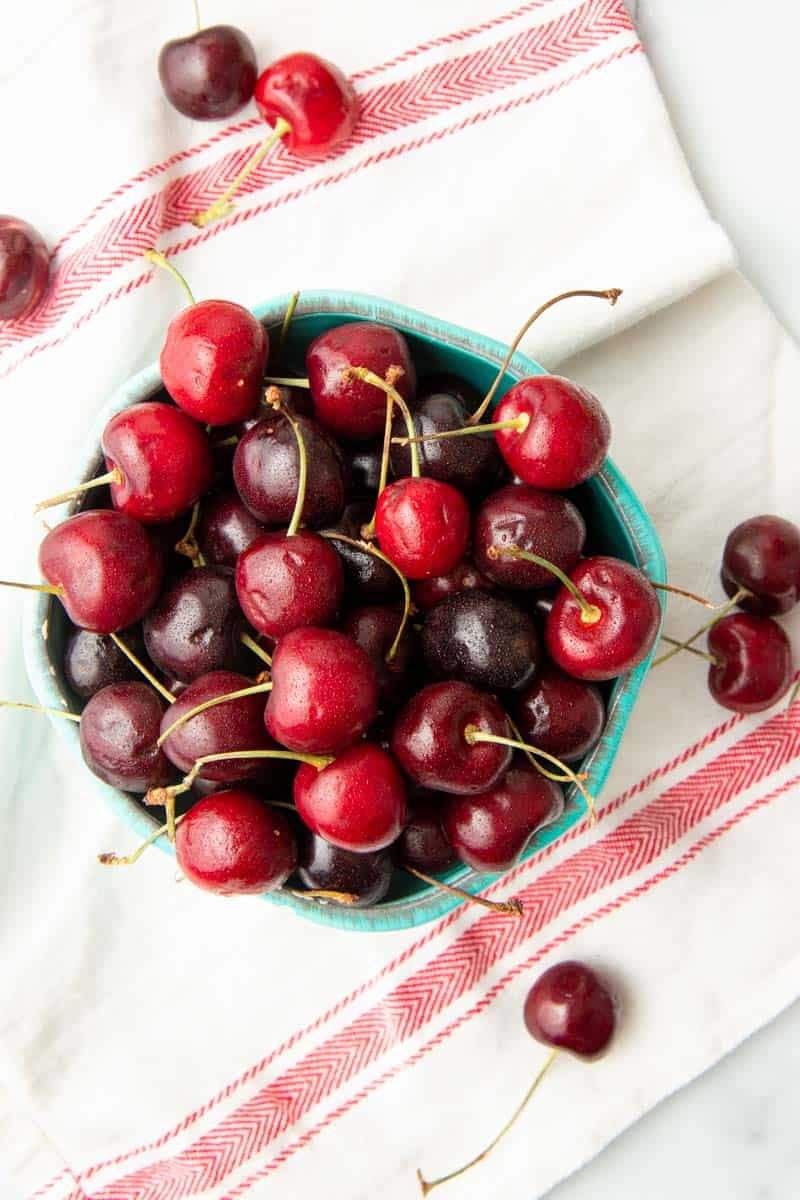Overhead of fresh cherries spilled onto a clean kitchen linen from an overflowing bowl.