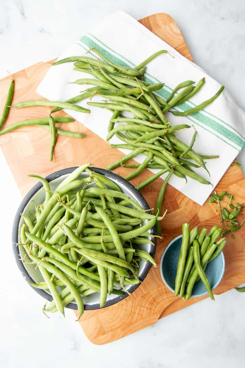 Overhead of fresh green beans in a bowl on a wooden cutting board alongside freshly snapped beans in another bowl.