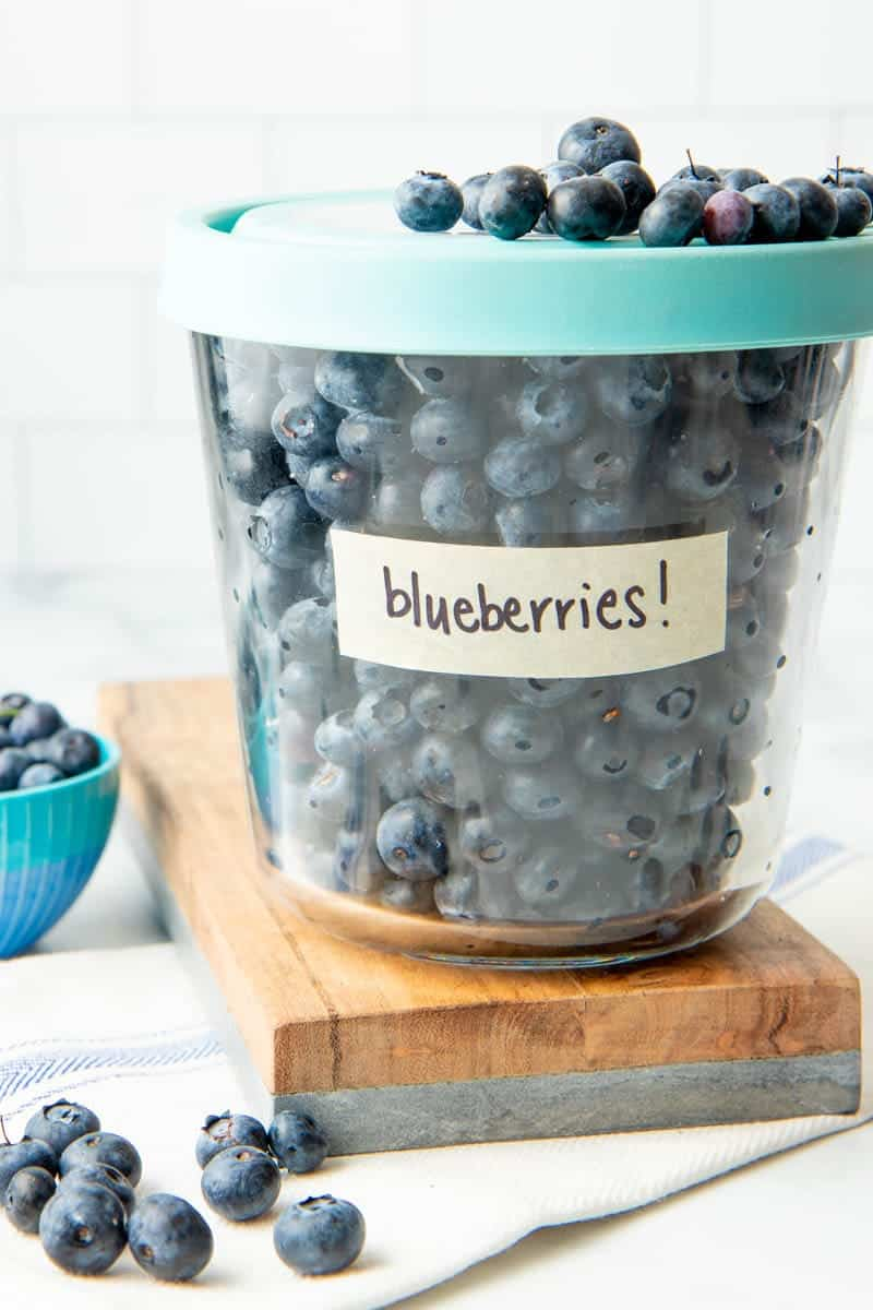 Close-up of tall glass freezer container with lid on, labeled and filled with individually frozen berries.
