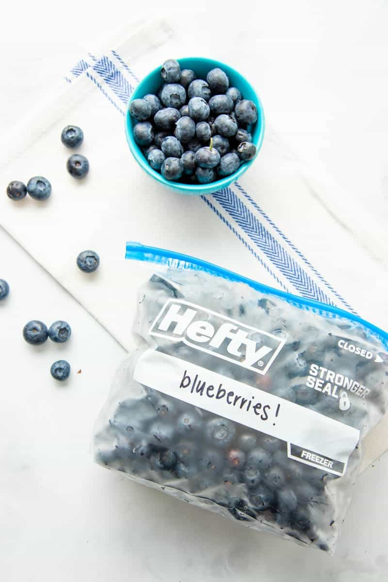 Overhead of Hefty freezer bag filled with individually frozen blueberries labeled and lying on its side.