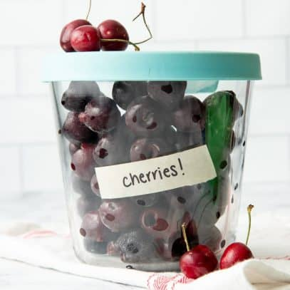 Tall glass container with lid, labeled and filled with individually frozen, pitted cherries.