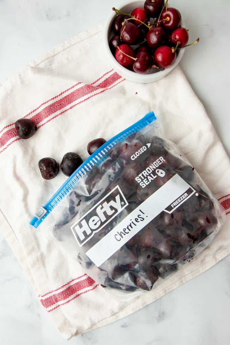 Overhead of open Hefty freezer bag lying on its side, filled with individually frozen, pitted cherries.