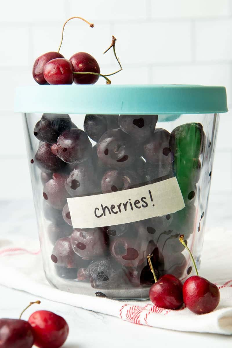 Close up of individually frozen, pitted cherries in a labeled glass container with a lid.
