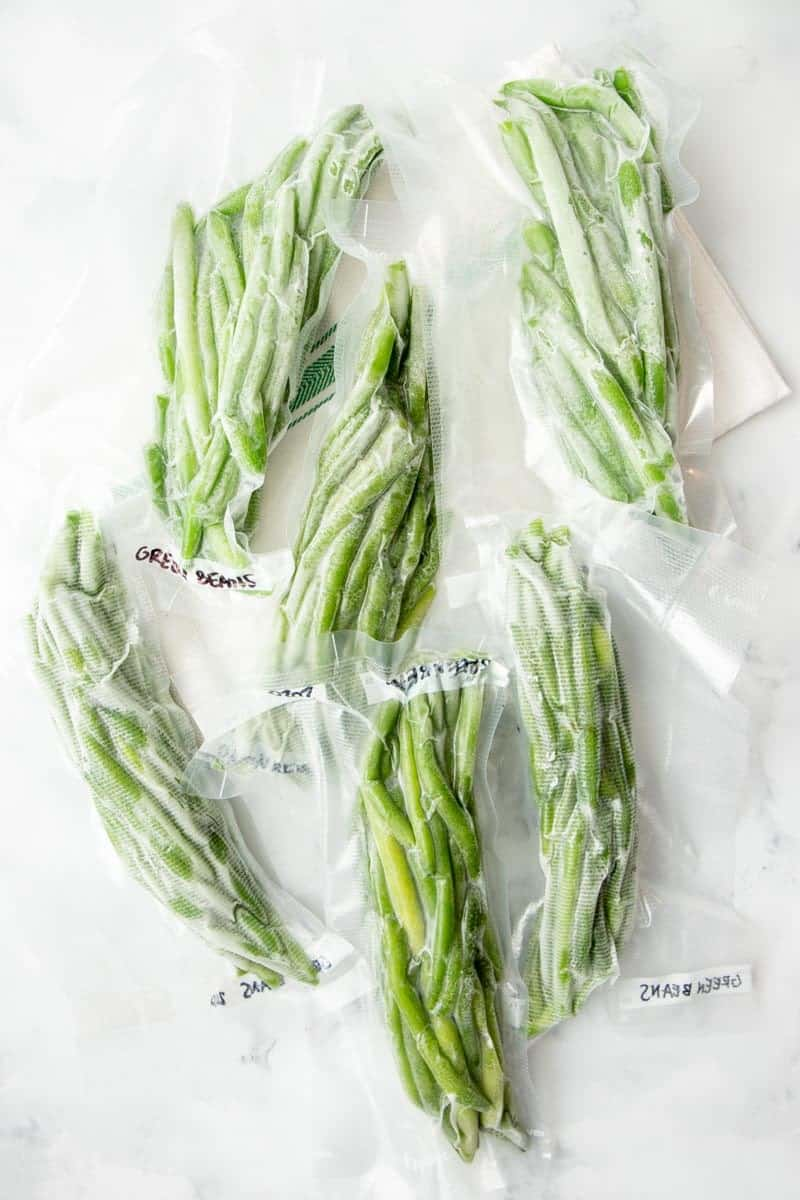 Overhead of frozen vacuum sealed packages of green beans.