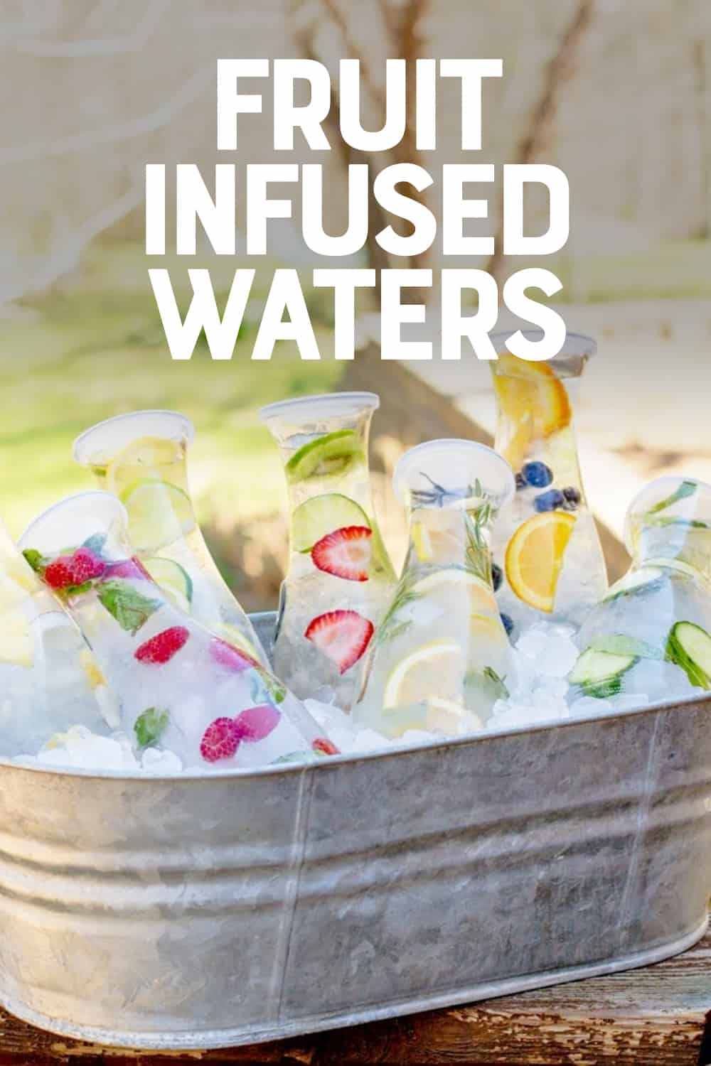 """Close-up of carafes filled with fruit infused waters sitting in a metal trough filled with ice. A text overlay reads, """"Fruit Infused Waters."""""""