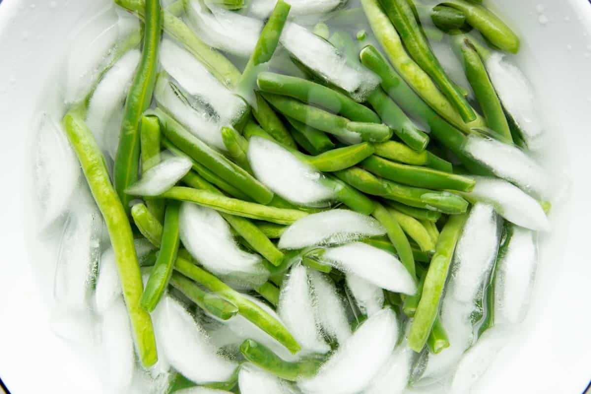 Overhead of blanched green beans in an ice bath.
