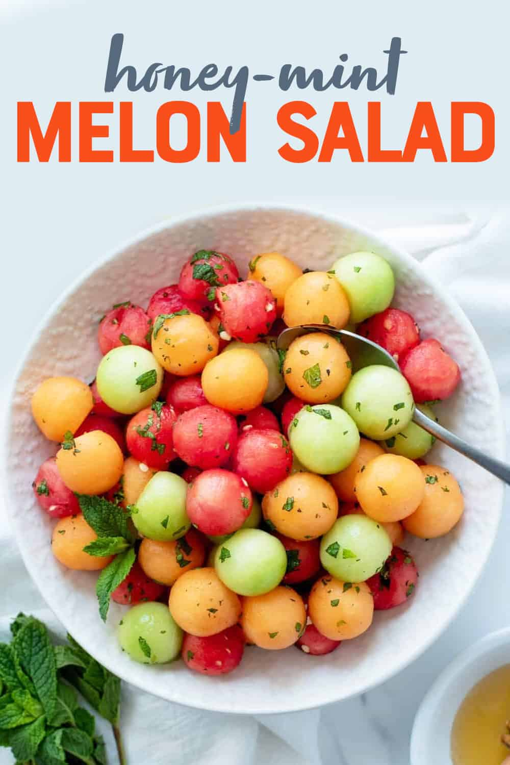 """Overhead of finished melon ball salad in a serving bowl with fresh mint and honey. A text overlay reads, """"Honey-Mint Melon Salad."""""""