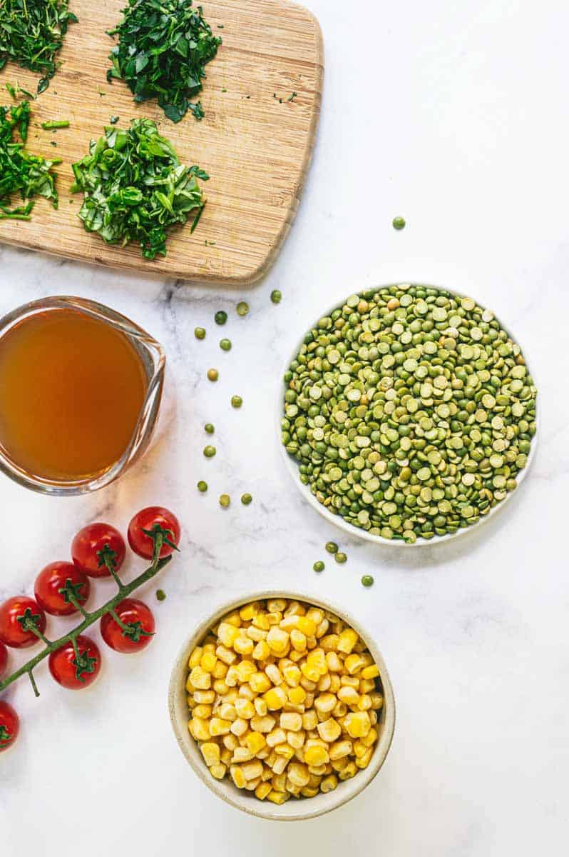 Ingredients for salad such as uncooked split peas, broth, frozen corn kernels, ripe cherry tomatoes on the vine, and chopped fresh herbs.