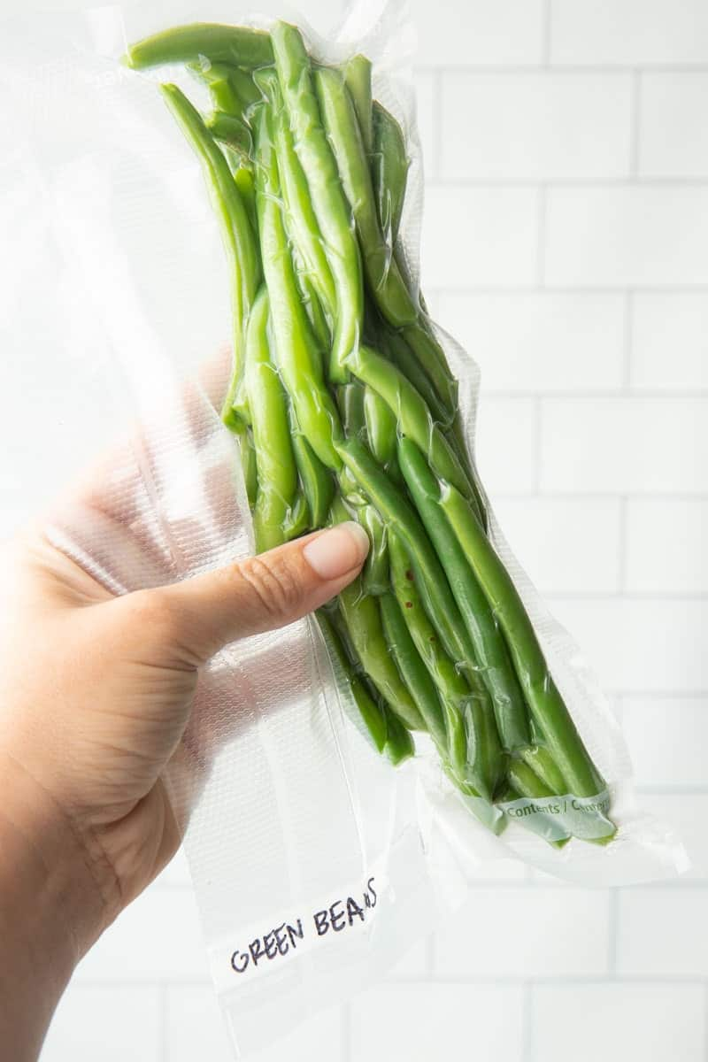 Close up of a hand holding a labeled and vacuum sealed pack of string beans.